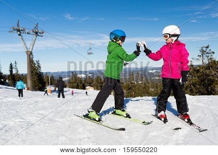 Two kids doing high five while standing on ski at the ski resort Trysil in Norway.