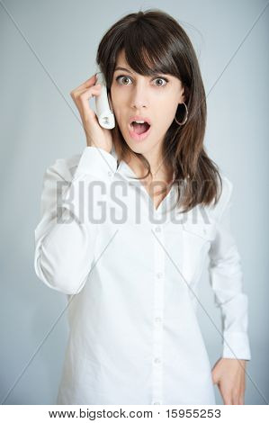 Young brunette talking on the phone with a surprised expression