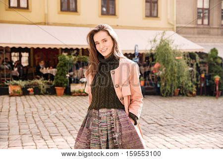 Portrait of smiling attractive young woman standing in old city