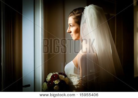 Bride at her wedding day she is looking out of the window