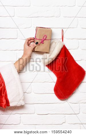 female hand gets present wrapped on craft paper from christmas stocking or xmas boot on white brick wall background