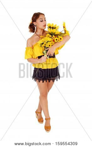 Gorgeous young woman in a yellow blouse holding a bunch of sunflowers looking at them standing isolated for white background.