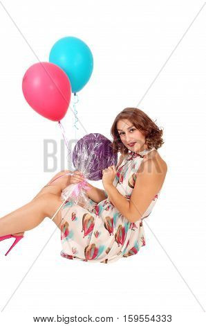 A beautiful young woman sitting on the floor holding two balloons and a lollypop isolated for white background.