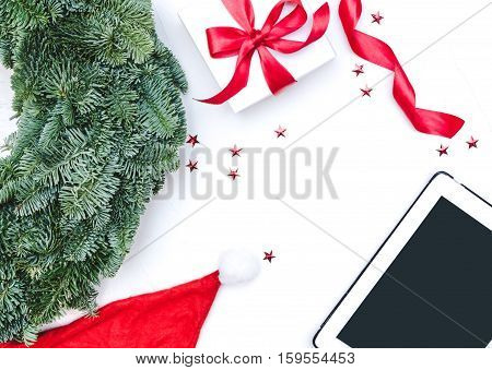 Flat lay Top view Christmas composition isolated on white background. Digital tablet natural green pine wreath white gift box with red fabric tape spiral ribbon stars confetti. Xmas background. Decor table.