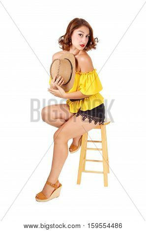 A lovely young woman sitting on a chair in black shorts and yellow blouse with a cowboy hat in her hand isolated for white background.