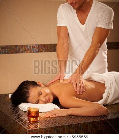 Young woman getting back massage in wellness center, relaxing with eyes closed.?