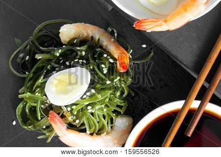 Delicious fresh seaweed salad with quail egg, seasame, soy sauce