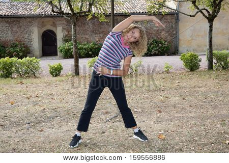 Senior Woman In Park Exercising After Running