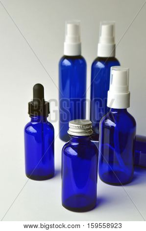 Group of dark blue glass bottles for cosmetic lotions, serums, oils and liquids