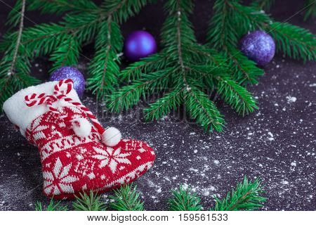 Christmas Red Stocking On Snowbound Black Background With Purple Balls
