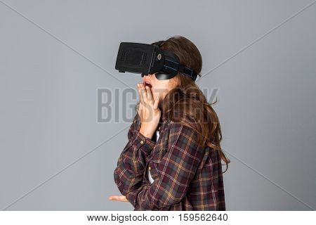 portrait of beautiful woman testing virtual reality glasses in studio on grey background