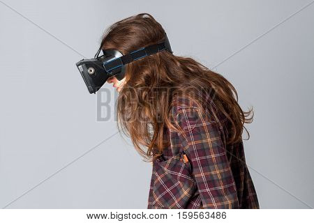 closeup portrait of cute woman in virtual reality helmet in studio on grey background