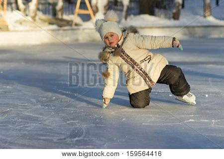 A child on a cold day in a warm jacket and hat fell to the ice skating.