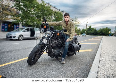 Handsome fashion man sitting on classical motorcycle and getting ready to ride in the city