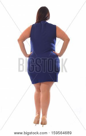 Full-body portrait of plus size model woman wearing XXL blue dress posing isolated on white background. View from the back.