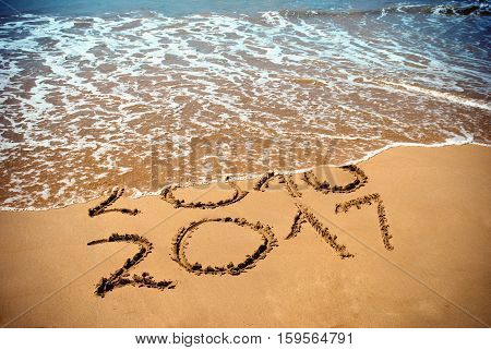 poster of New Year 2017 is coming concept - inscription 2017 and 2016 on a beach sand the wave is covering digits 2016. New Year 2017 celebration on New Year tropical island travel tour.
