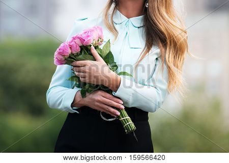 beautiful young girl with a bouquet of pink rose flowers