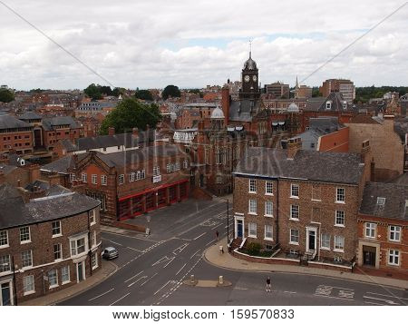 Modern buildings mixed with old in a town in England where people stroll on a summer day.