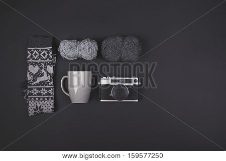Minimalist setup of winter objects in gray. Vintage analogue camera, two wool yarns, winter print socks and coffee mug on dark gray background. High angle view, copy space.