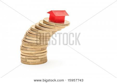 Small model house stacked on top of a pile of coins isolated on white background