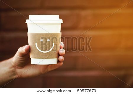 Paper cup of happy takeaway coffee in the hand. Holder with happy smile, because coffee is always a good idea. Toning of evening sunlight.