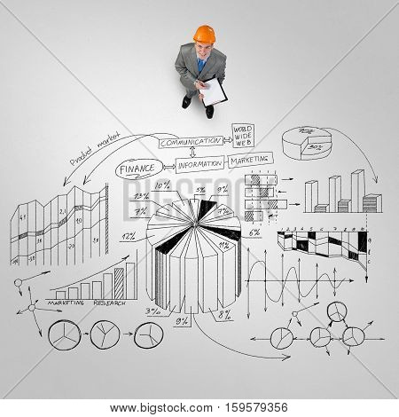 Top view of engineer man with folder and plan sketches on floor