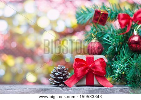 Close up of handcraft gift box with red ribbon and pinecone on wooden table for Christmas or New Year decoration background