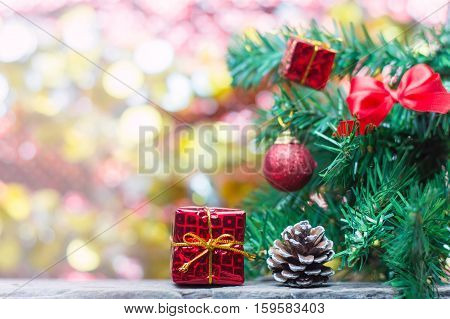 Close up of red gift box and pinecone on wooden table for Christmas or New Year decoration background