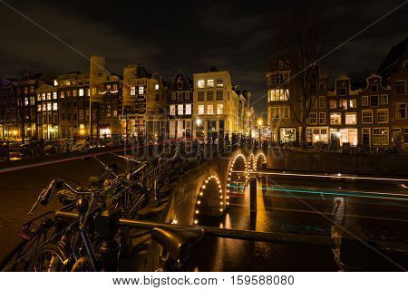 Light trails of cars and boats in the canals of Amsterdam during Amsterdam Light Festival