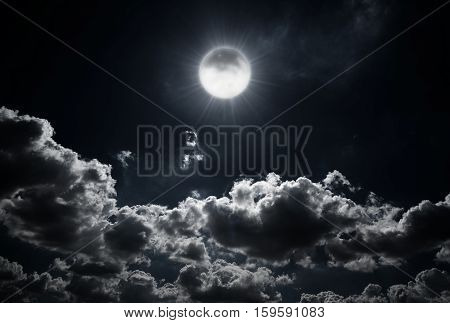 Dramatic photo illustration of a nighttime sky with brightly lit clouds and large. Beautiful starry night sky with clouds and bright full moon or super moon.