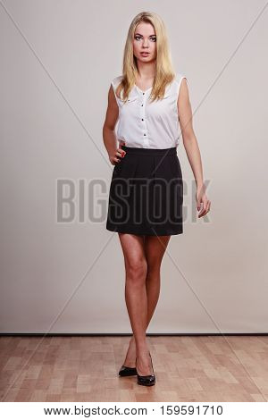 young woman in trendy short black skirt posing in full length studio portrait on gray background