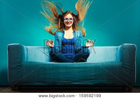 Fashionable Girl Wearing Denim Sitting On Couch.
