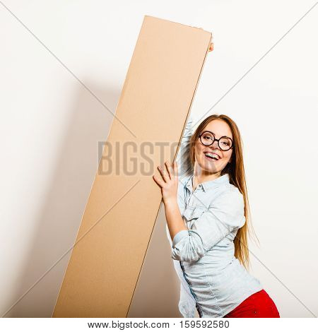 Happy woman moving into new apartment house carrying carton box with furniture. Young girl arranging interior and unpacking.