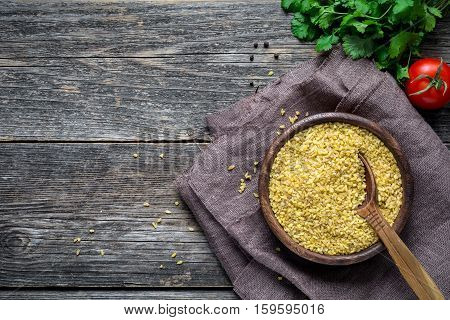 Bulgur (dry wheat grains) in wooden bowl, fresh parsley, tomato and spices on wooden table background. Top view with copy space for text