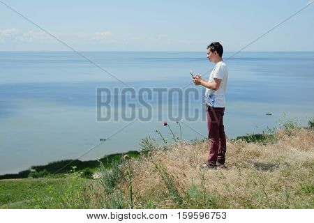 the guy on the beach with a tablet looking into the distance at sea the concept of technology