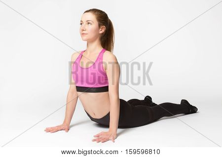 Beautiful Sporty Fit Young Woman In Sportswear Working Out. Model Doing Cobra Asana, Bhudjangasana (