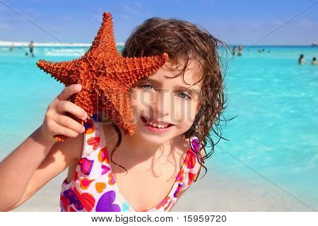 little beautiful  tourist girl holding starfish tropical beach