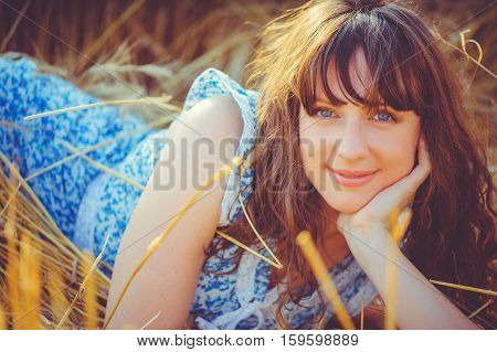 Girl Lying In A Wheat Field During