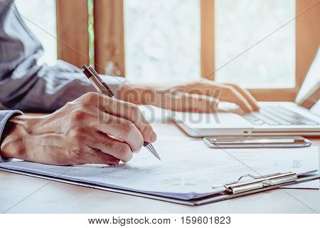 Business man hand working with laptop computer and writing business graph or analysis chart on modern desk table. close up. Business concept