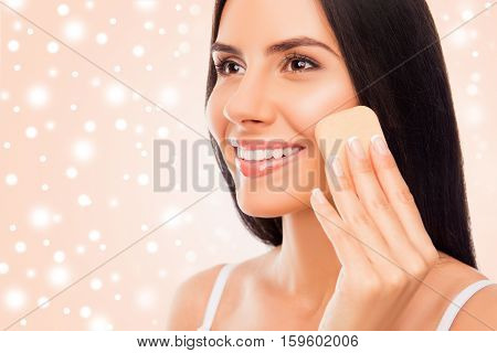 Happy  Woman With Sponge Doing Professional Make-up On The Snowy Background