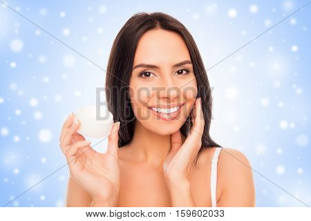 Pretty Woman  Applying Cream On Her Face On The Background Of Snowfall