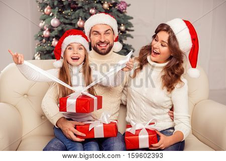 Happy Excited Parents Looking How Daughter Opening Xmas Present
