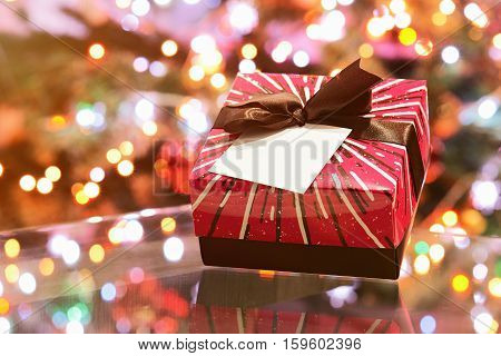 colorfull present box on glass table blurred christmas background