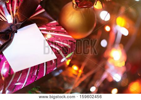 christmas brown gift box in glitter lights . Present for new year on christmas tree