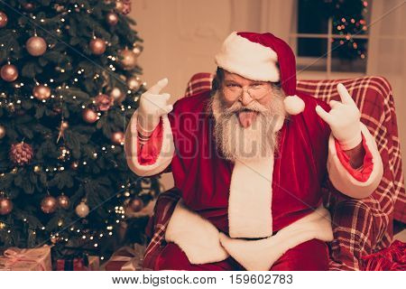 It's Party! Cool Santa Claus Showing Tongue Out And Gesturing With Fingers Rock-and-roll Near Christ