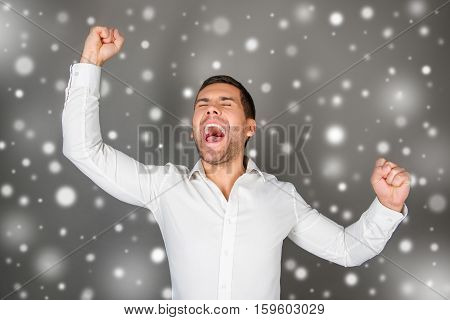 Excited happy l man triumphing with raised hands on snowy background