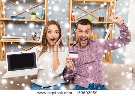 Happy Man And Woman Screaming With Laptop And Bank Card And Buying Presents For Christmas