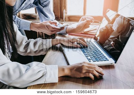Two colleagues discussing data with smart phone and new modern computer laptop on desk table. Close up business team concept.