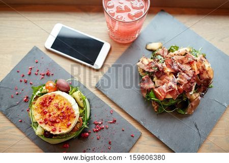 food, eating and technology concept - goat cheese and prosciutto ham salads on stone plates with smartphone and glass of drink at restaurant or cafe
