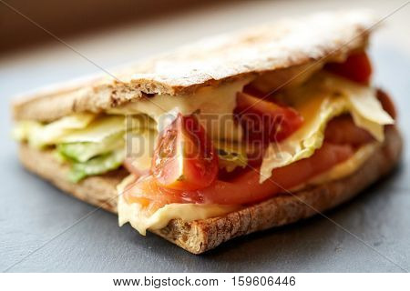 food, dinner and eating concept - salmon panini sandwich with tomatoes and cheese on stone plate at restaurant